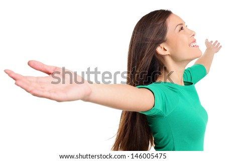 Free happy elated woman with arms out raised up in serene joyful pose. Girl in green shirt isolated on white background in studio. Mixed race Asian Caucasian female model. - stock photo