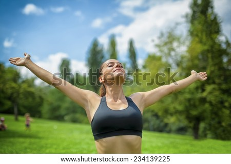 free happy young fit woman in nature raised her arms and feeling the sun. Freedom concept. - stock photo