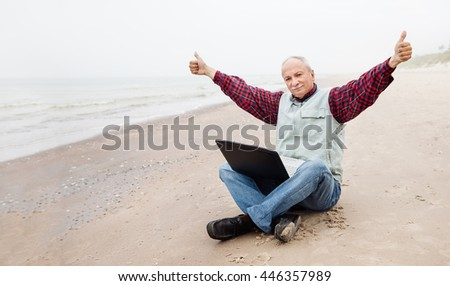 Free lifestyle concept. Happy senor businessman sitting on the beach on a foggy day with a laptop and enjoys a successful deal