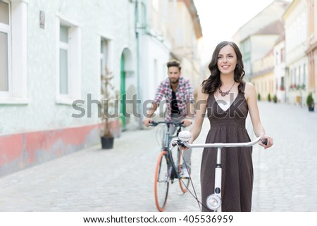 free people having fun with bikes on a pedestrian area between historical buildings and the girl is in front of the guy - stock photo