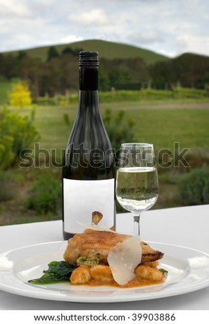 Free Range pan-seared Chicken Breast Fillet filled with Soft Cheese and Pesto, set on Gnocchi, topped with a Tomato & Basil Sauce, accompanied by a glass of Chardonnay