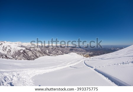 Free ride ski tracks on snowy slope. Fresh powder snow in a bright day of winter season. Wide angle panoramic view, italian Alps. - stock photo