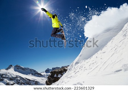 Free rider with snowboard jumping from hill