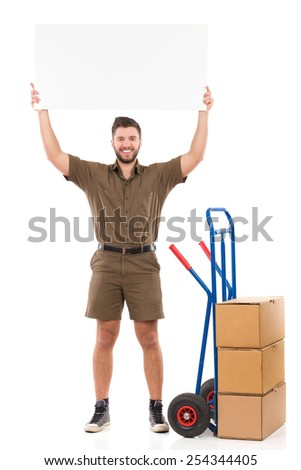 Free Shipping Day. Happy delivery man standing and holding a blank banner over his head. Full length studio shot isolated on white. - stock photo
