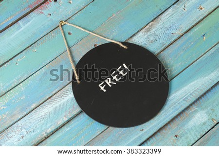 Free sign on blue wood background - stock photo