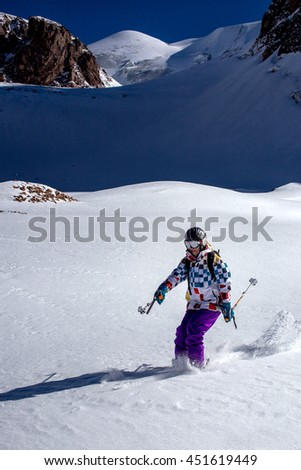 Free skier girl riding from glacier - stock photo