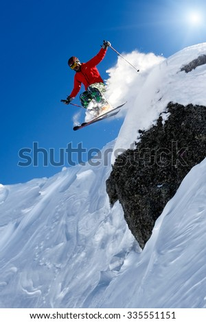 Free skier jumping from rock
