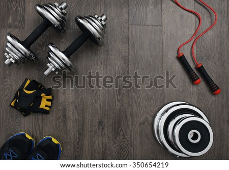 free space on the wooden floor surrounded fitness equipment - stock photo