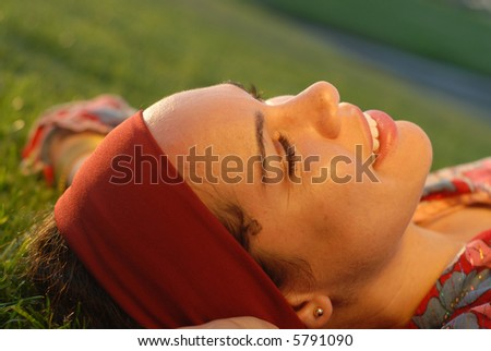 Free spirited young woman enjoying a moment of peace in the park - stock photo