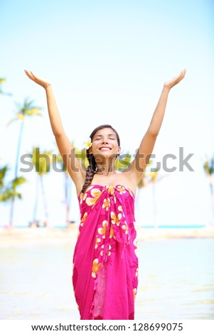 Free spiritual girl on hawaii on beach in meditation freedom pose enjoying Hawaiian beach smiling serene and happy looking up. Multicultural mixed race Asian / Caucasian girl in sarong. - stock photo