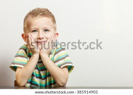 Free time, fun and expression. Little boy play indoors make silly gestures face emotions. Blonde child sit hold head with hand. - stock photo
