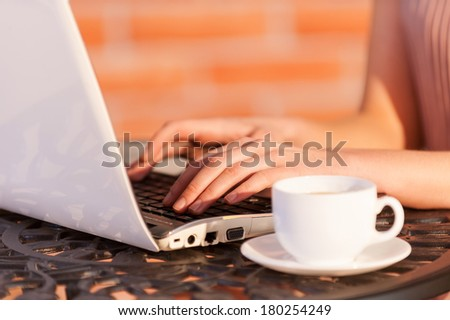 Free Wi-Fi zone. Cropped image of woman working at laptop while sitting at the outdoor cafe - stock photo