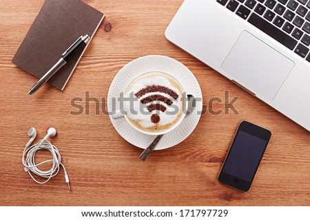 Free wifi area sign on a latte coffee in a business table - stock photo