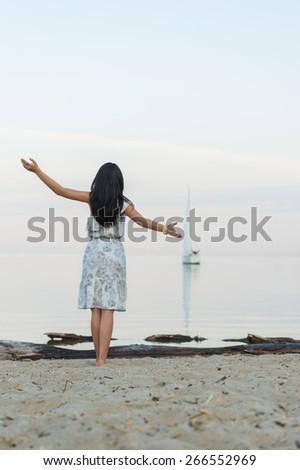 Free woman enjoying freedom feeling happy at beach at morning. Beautiful serene woman and welcoming yacht and sailor with arms opened outstretched up. Hispanic Caucasian female model - stock photo