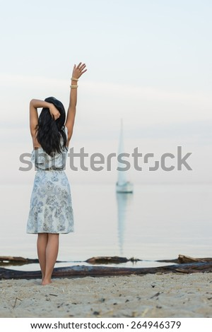 Free woman enjoying freedom feeling happy at beach at morning. Beautiful serene  woman in happiness and welcoming yacht and sailor with arms opened outstretched up. Hispanic Caucasian female model - stock photo
