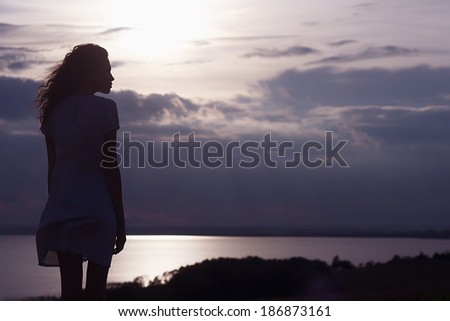 Free woman enjoying freedom feeling happy at beach at sunset. Beautiful serene relaxing woman in pure happiness and elated enjoyment with arms raised outstretched up. - stock photo