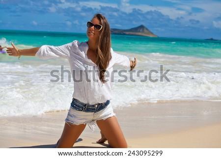 Free woman enjoying freedom feeling happy on the Hawaiian beach. Sea, sun and summer fun. Beauty in the summer sun. - stock photo