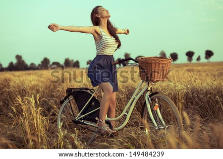 Free woman enjoying freedom on bike on wheat field at sunset - stock photo