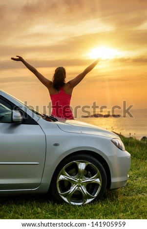 Free woman on car travel looking summer sunset sky and ocean. Female driver leaning on car bonnet raising arms to glow dusk sun. Traveling and freedom concept. Copy space.