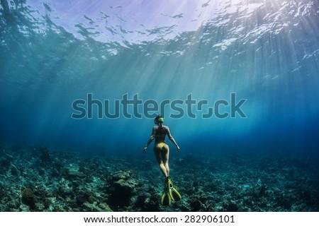 Freediver Girl in yellow bikini wearing yellow fins beholding beautiful coral reef underwater. Maldivian diving with rays of Sun. - stock photo