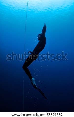 Freediver moves out of the depth of the ocean - stock photo