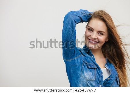 Freedom and joy. Young attractive happy girl enjoy her life. Smiling positive woman wearing stylish jeans clothes with blowing long hair. - stock photo