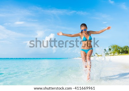 Freedom carefree girl playing splashing water having fun on tropical beach vacation getaway travel holiday destination. Playful woman with abs slim bikini body relaxing feeling free.  - stock photo