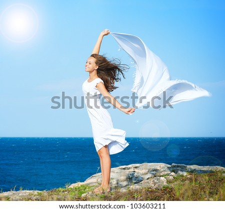 Freedom Concept.Beautiful Girl with White Scarf standing on the Rock. Flying.Free.Vacation