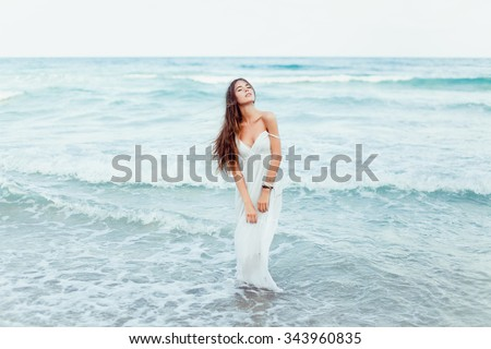 Freedom concept,Beautiful sexy young woman brunette hair evening makeup wearing short dress suit top skirt,tropical island LA,California.walks summer fall collection,perfect outfit in ocean view - stock photo