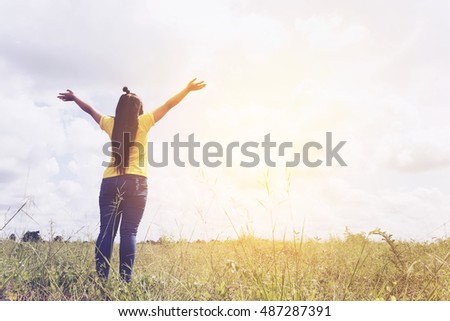freedom concept : beautiful woman enjoying fresh air and nature at meadows, sunset tone