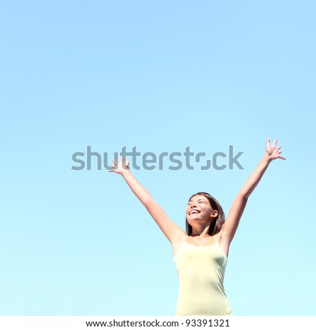 Freedom concept. Free woman smiling happy with arms raised joyful under clear blue sky. Beautiful young multiracial Asian / Caucasian girl in her 20s. - stock photo