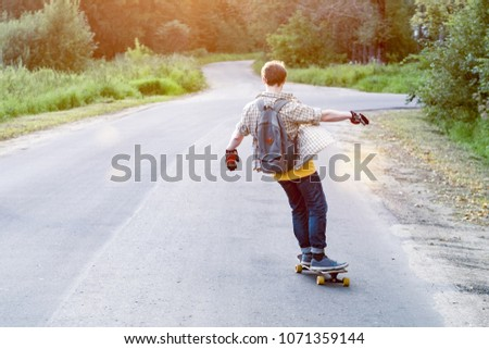 Freedom concept. Hipster rides on the road in the Park on a skateboard. A man rides longboard