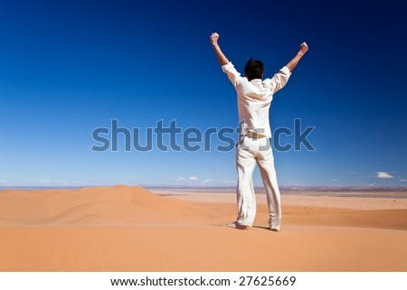 Freedom concept: Rear view of an adult white man standing on a sand dune and holding arms up. Erg Chebbi, Maroc - stock photo