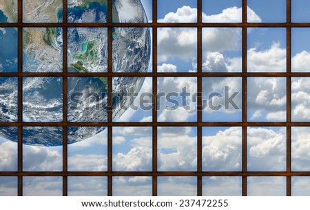 Freedom concept: the world through a grating Conceptual image with image from NASA - stock photo