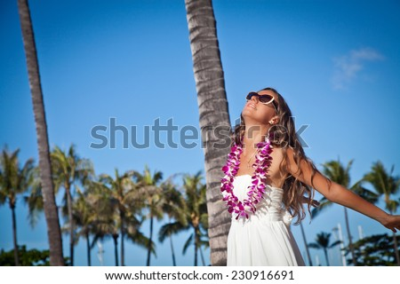 Freedom concept, woman with welcoming Lei and with arms raised on the beach. Shot of an attractive young woman enjoying the sunshine. Hawaiian Island of Oahu - stock photo