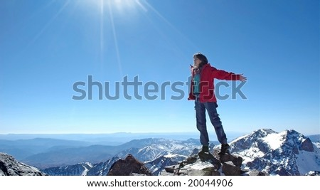 Freedom! Girl over a snow capped peaks with outstretched arms. - stock photo