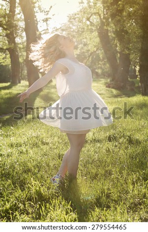 Freedom. Gorgeous blonde woman spinning around, enjoying a beautiful summer day in the nature. - stock photo