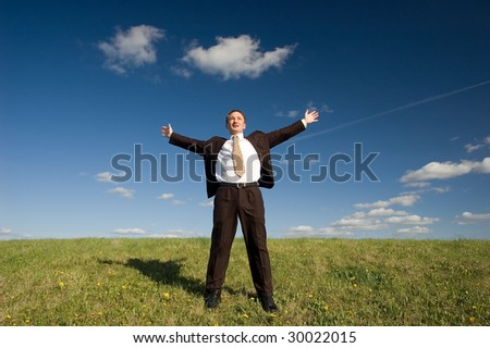 Freedom - Happy business man standing on green grass - arms outstretched