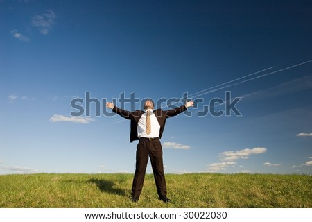 Freedom - Happy business man standing on green grass - arms outstretched - stock photo