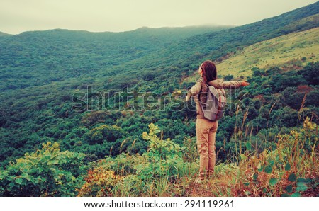 Freedom happy traveler woman standing with raised arms and enjoying a beautiful nature. Image with instagram color effect - stock photo