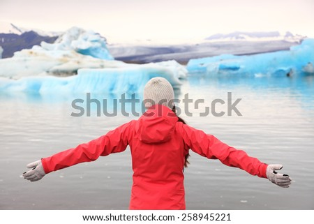 Freedom happy woman at glacier lagoon on Iceland serene and blissful. Tourist girl serene enjoying view of Jokulsarlon glacial lake. Woman in beautiful Icelandic nature landscape looking at iceberg. - stock photo