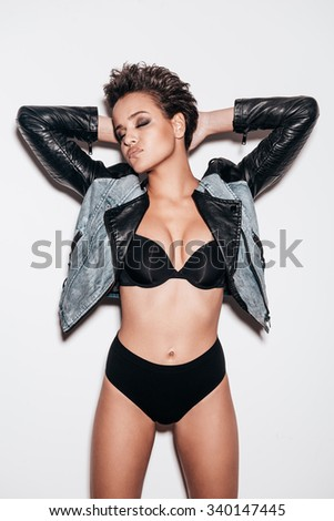 Freedom is in her blood. Beautiful young short hair woman in black underwear and leather jacket keeping hands behind head and eyes closed while posing against white background - stock photo