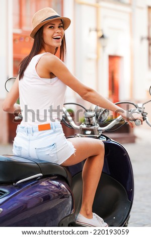 Freedom is in her veins. Rear view of beautiful young woman in funky hat riding scooter and smiling - stock photo