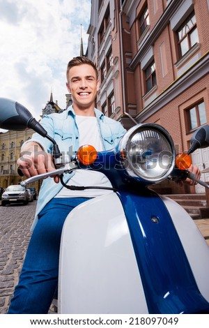 Freedom is in my veins! Low angle view of handsome young man riding scooter along the street and smiling  - stock photo