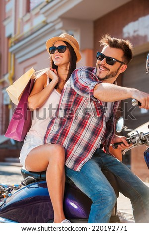 Freedom is in their veins. Side view of beautiful young couple riding scooter together while happy woman carrying shopping bags and bonding - stock photo