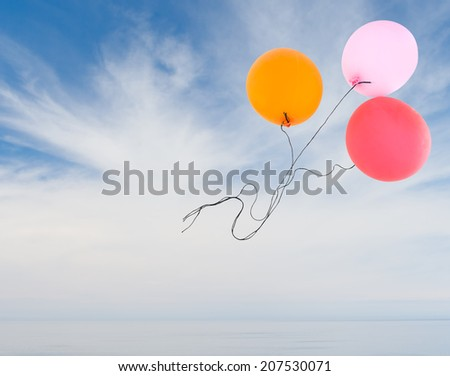 Freedom, liberty, dreams etc concept. Red orange and pink party balloons fly away over dramatic real sky and calm sea background. - stock photo