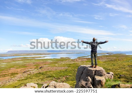 Freedom man in nature on iceland with arms enjoying free happiness in beautiful icelandic landscape.   - stock photo
