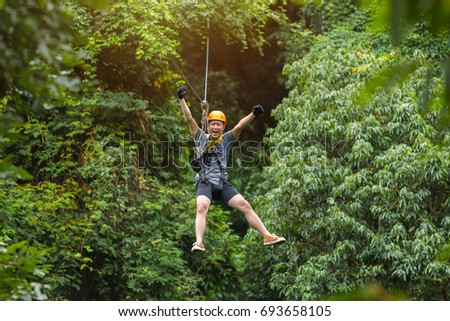 Freedom Man Tourist Wearing Casual Clothing On Zip Line Or Canopy Experience In Laos Rainforest