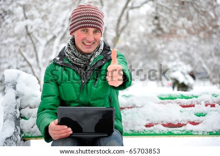 Freedom - Man using a laptop outdoor in winter park with copyspace - stock photo