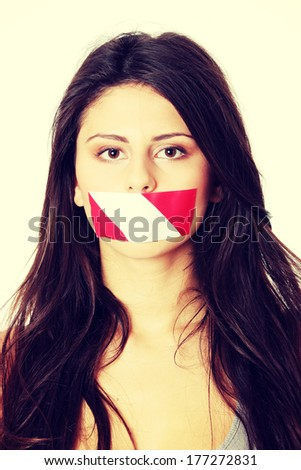 Freedom of speech concept. Young beautiful woman with red and white tape on her mouth. Isolated on white